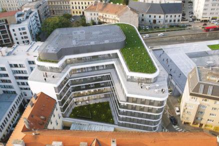 Na fotografii dobre vidieť tvar budovy a zelenú strechu.