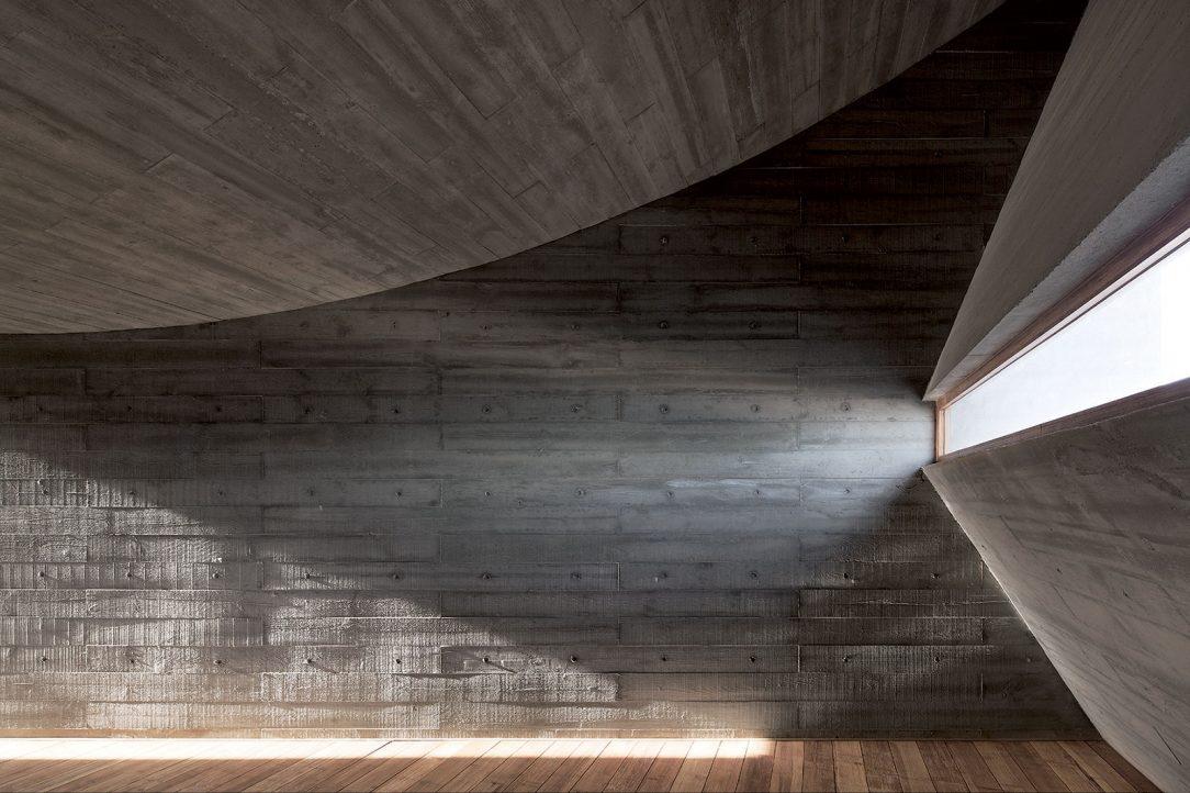 Strohý betónový zjav knižnice chceli Vector architekti poľudštiť arozhodli sa na to použiť klasickú metódu latového šalovania. Jednotný monolit tak získal jemný detail dreveného reliéfu. Kidei odtlačkov ich priviedli šľapaje vpiesku, ktoré sú stopou prítomnosti človeka. Foto: Xia Zhi