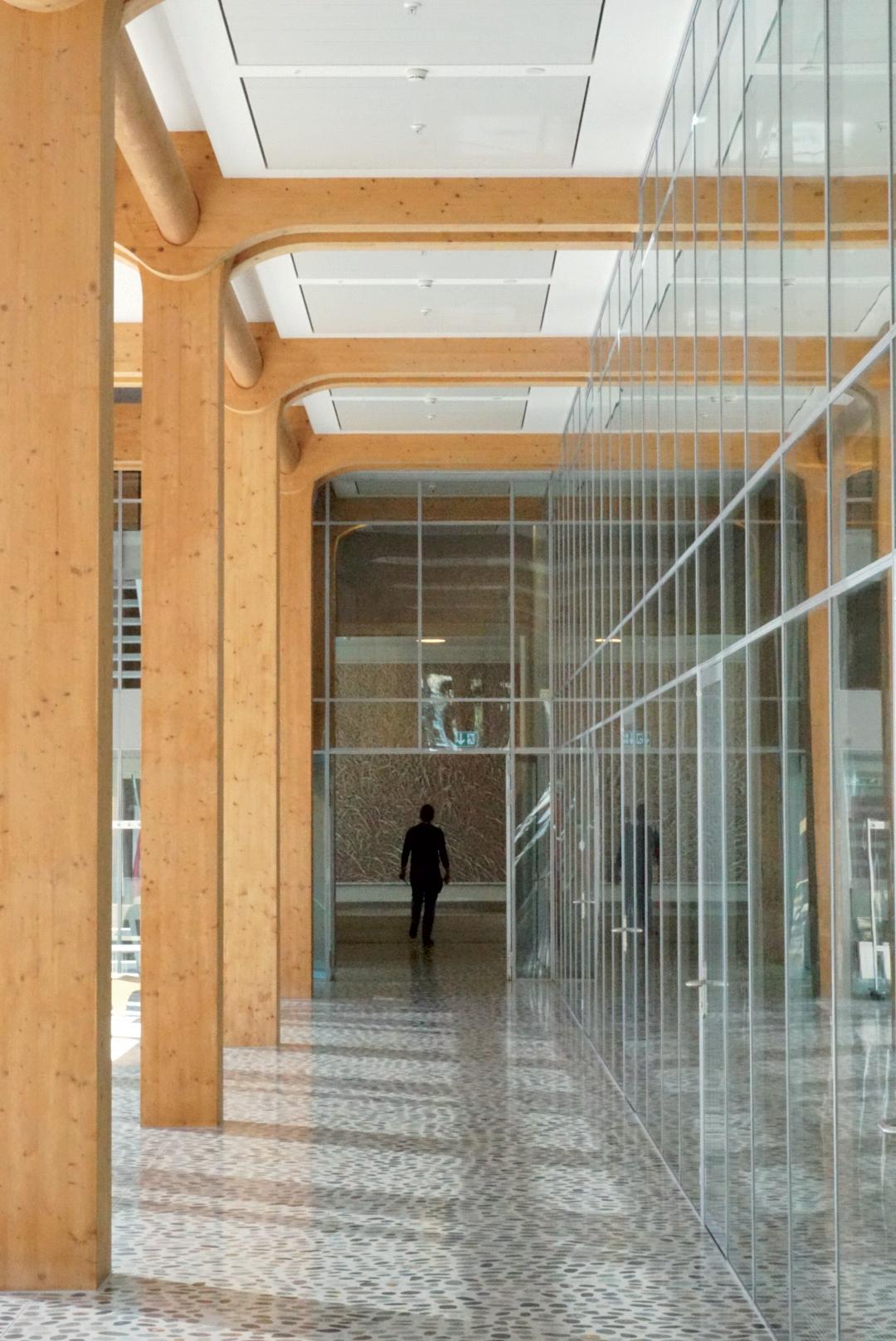 Svetlá drevená konštrukcia 7-podlažnej kancelárskej budovy od Shigeru Bana je nielen nositeľom identity, ale aj jedinečného detailu, environmentálneho charakteru apríjemného pôsobenia vpracovnom prostredí.