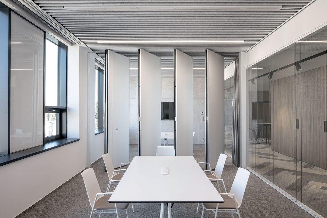 Monochromaticky riešené zasadacie miestnosti s akustickými materiálmi sú predelené posuvnou stenou.