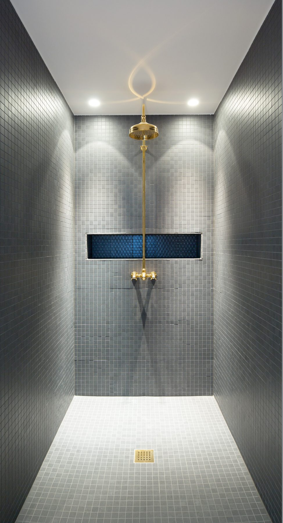 Sprchový kút je obložený malými sivými obkladačkami ktoré nechávajú vyniknúť sprchovú hlavicu batériu a odtokovú mriežku z mosadze.