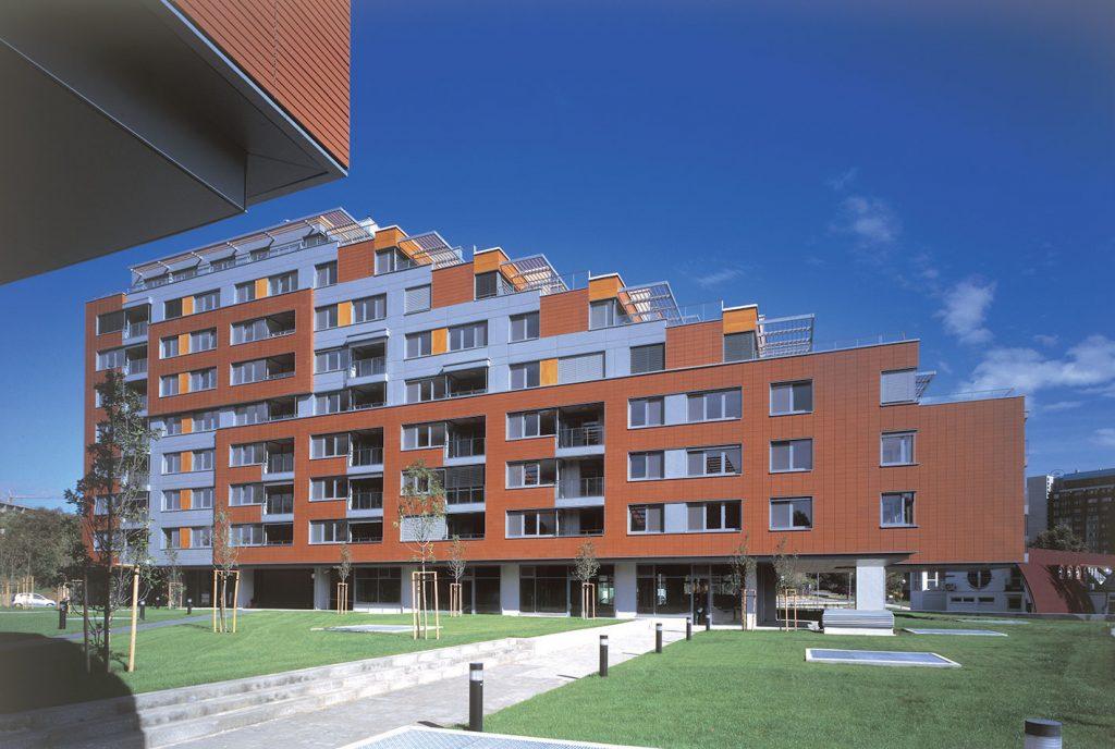 Bytové domy Karloveské rameno, Bratislava, 2002 – 2006 (Karol Stassel, Juraj Šujan). Víťazný návrh architektonickej súťaže. Dva terasovité objemy klesajúce k prírodnému prostrediu zátoky s bytmi a vybavenostným parterom.