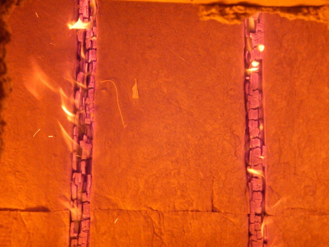 Pohľad na skúšobné pece v 80. minúte skúšky – zreteľné postupné horenie drevených vrstiev a dokonalá izolačná funkcia kamennej vlny