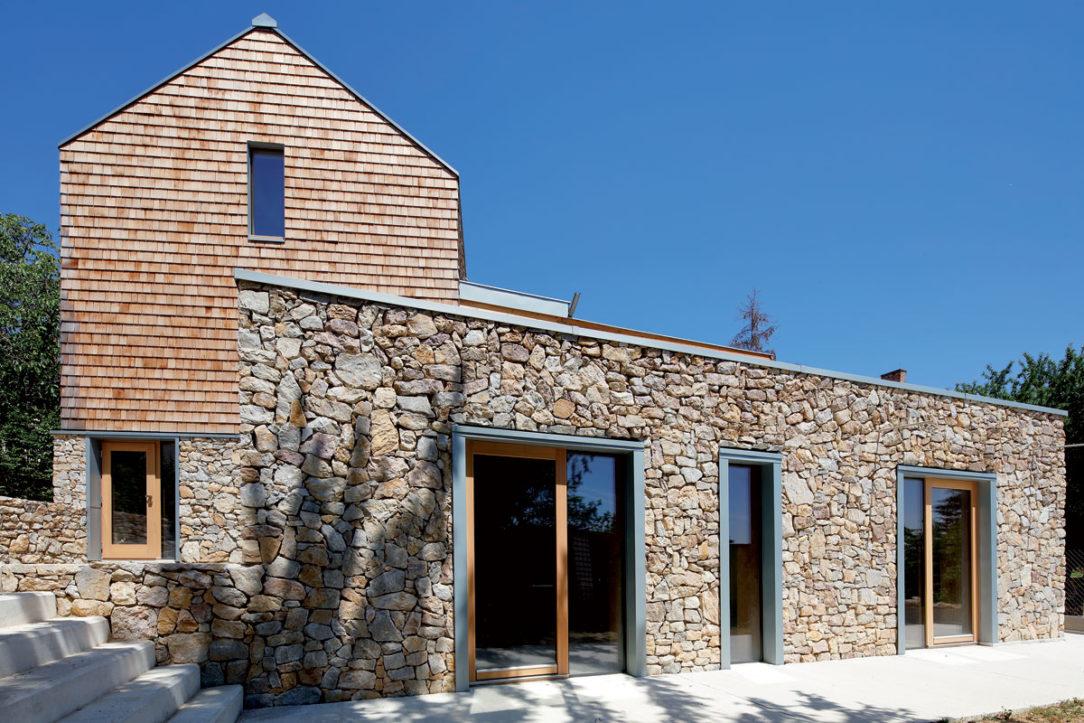 Rámy okien a dverí sú skryté za titánzinkovými obložkami vďaka ktorým vznikla čistá kombinácia skla kovu a kameňa.