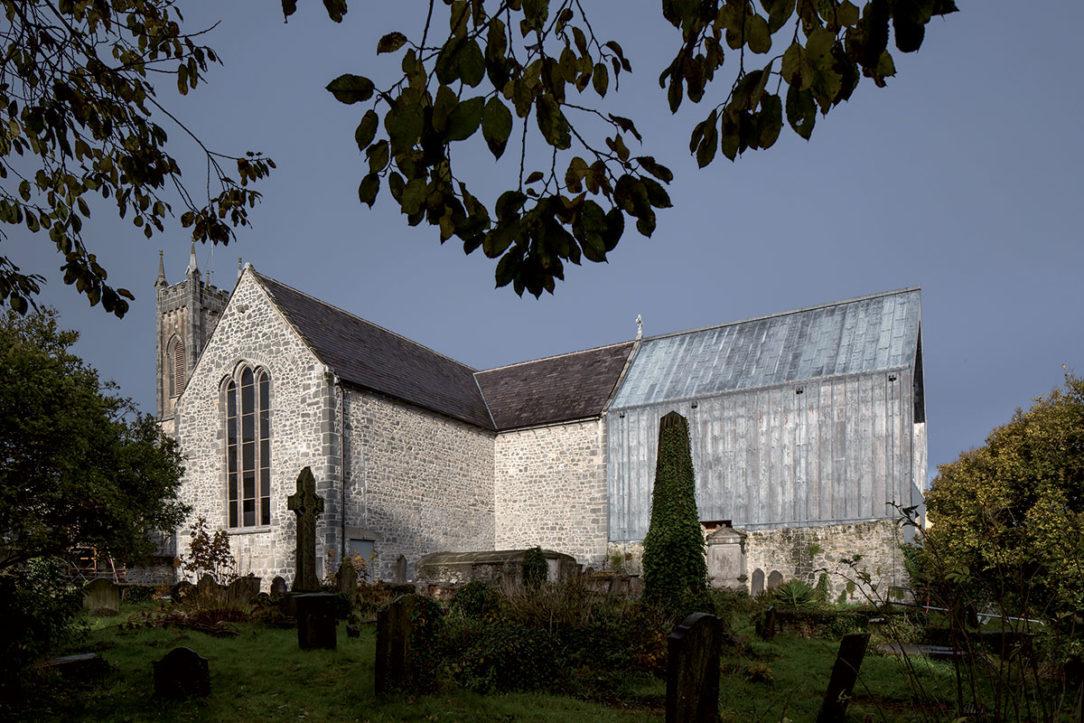 Olovený plech odlišuje nové objemy od staršej hmoty. Dobudované presbytérium obnovilo siluetu kostola.