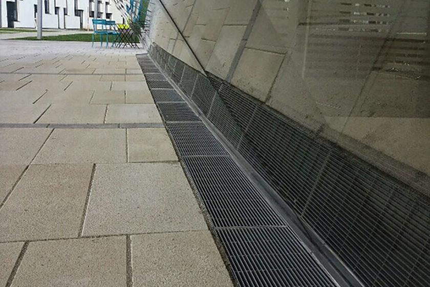 Polyfunkčný objekt s osadeným nerezovým fasádnym žľabom po celom obvode. Použitý je Pozdĺžne rebrovaný rošt.