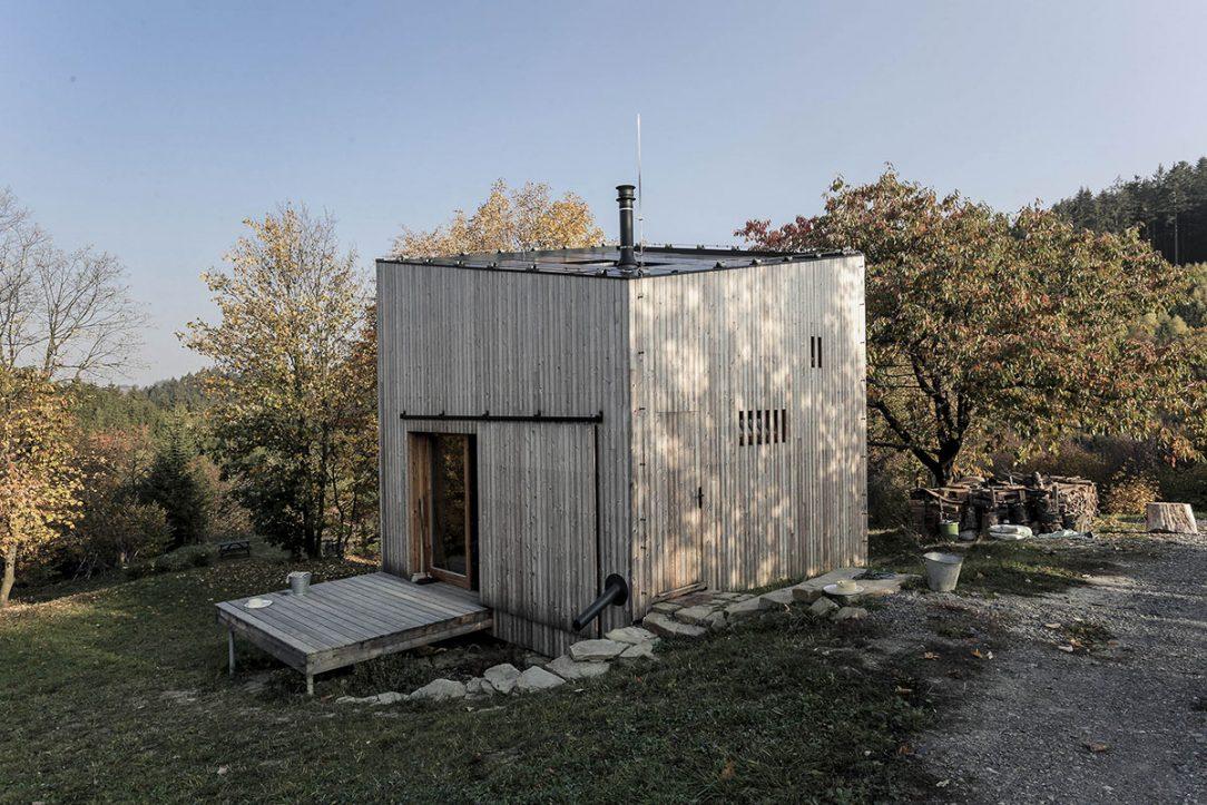Nad pivnicu na betónovú dosku architekti postavili jednoduchú drevenú kocku s priečkovou hrazdenou konštrukciou