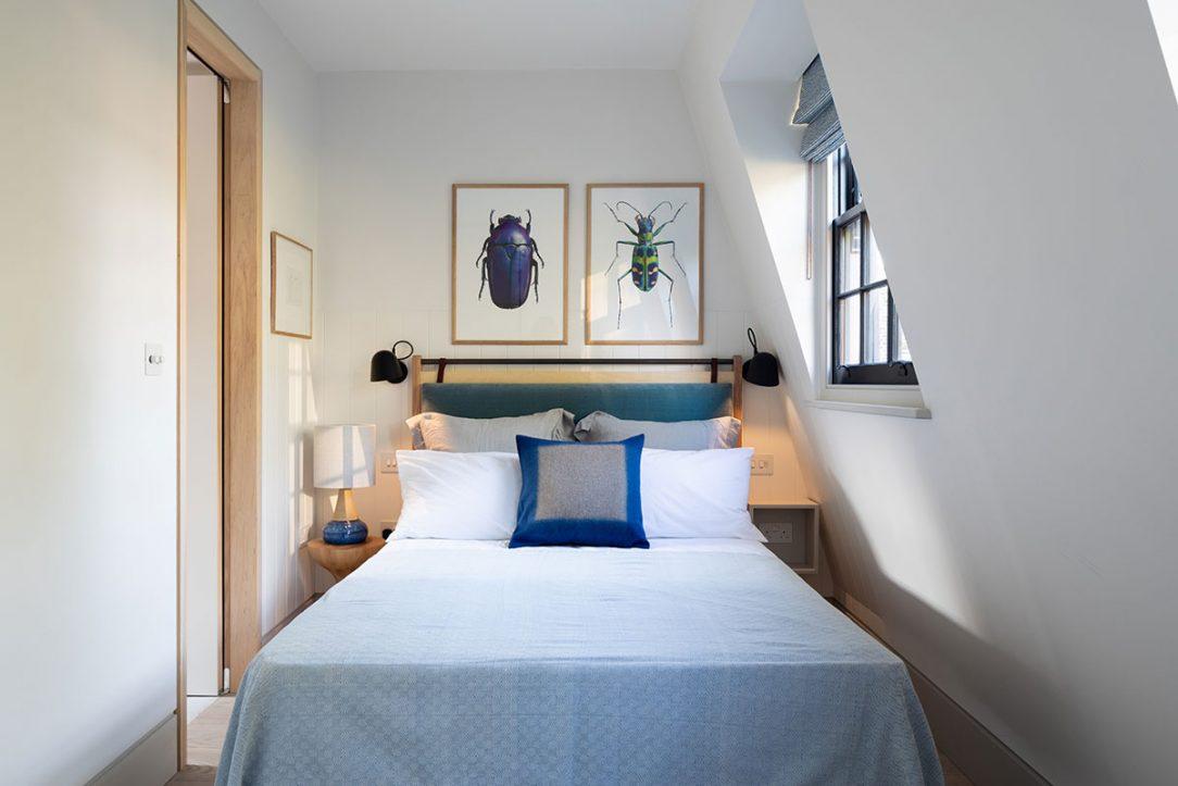 Umelecké plagáty a textílie na posteli dopĺňajú svetlú paletu farieb v spálni