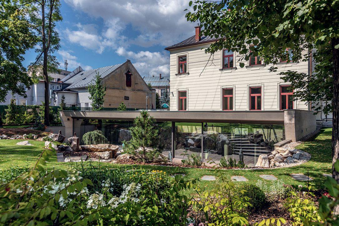 Nová prístavba je zapustená do terénu. Nekonkuruje historickému objektu a vďaka zelenej streche sa stráca v záhrade.