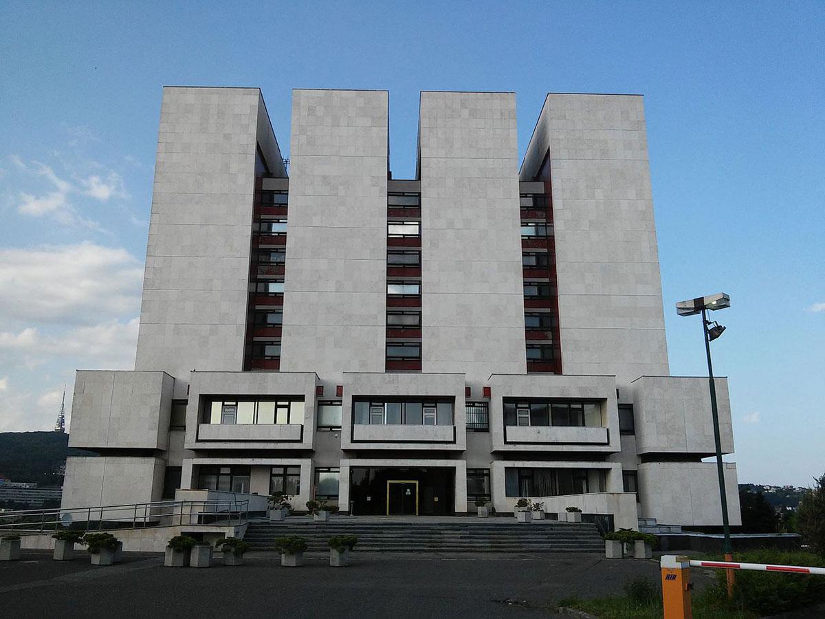 Prísna a geometricky členená fasáda Slovenského národného archívu (1983) odkazuje na štruktúru depozitára a úložných priestorov. Ikonický až brutalistický výraz mal byť zmiernený výsadbou stromov, ktorá sa však nezrealizovala.