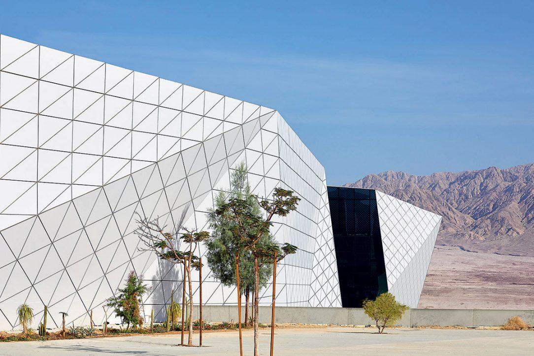 Lomená fasáda z bielych hliníkových trojuholníkov.