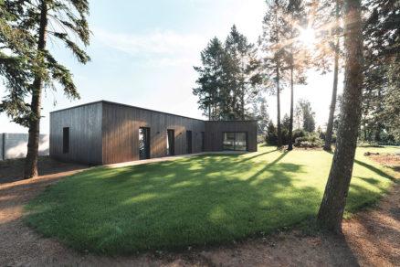 Projekt bungalova pôsobí v prírodnom prostredí nenápadne s okolím splýva i vďaka tmavej drevenej fasády.
