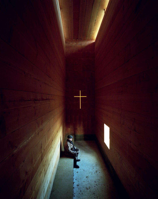 Malé okno kríž z farebného skla a vysoko posadený svetlík sú jediné zdroje svetla v interiéri kaplnky.