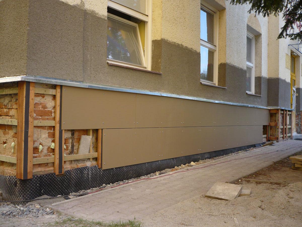 Montáž cementotrieskových dosiek tvoriacich obklad spodnej časti stavby.