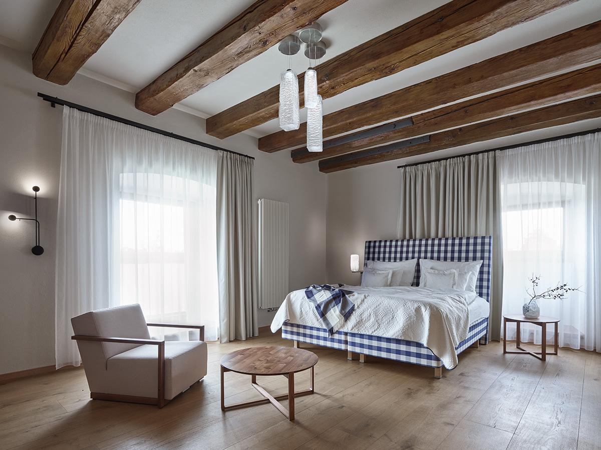 Priestranné hotelové izby majú doskové podlahy, robustné drevené dvere a vstavaný nábytok.