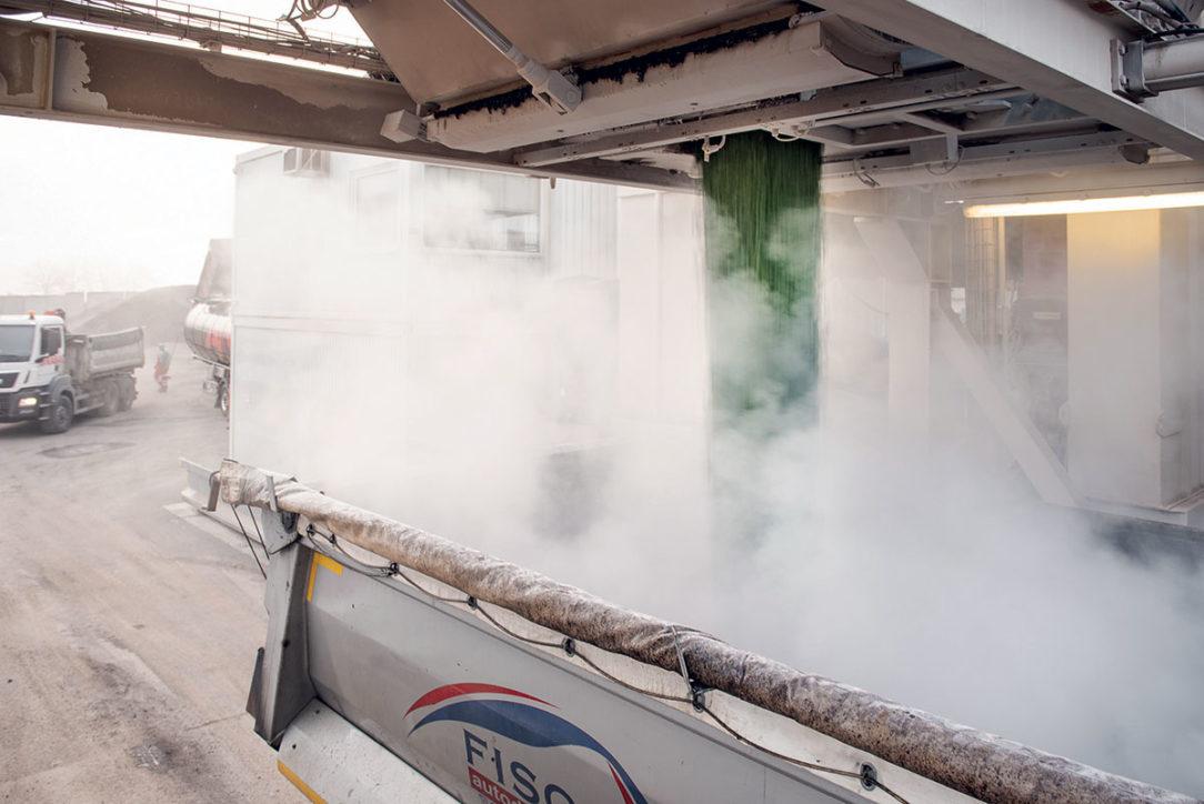 Pohľad na výstup zelenej asfaltovej zmesi z výrobne (obaľovacej súpravy v Hanušovciach nad Topľou)