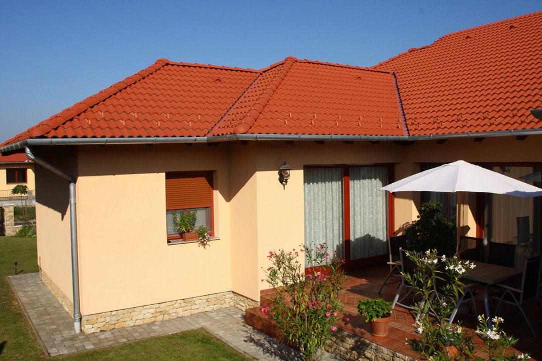 Tehlovo červená krytina v klasickom štýle, na mierne členitej streche valbového typu. Krytina veľmi pekne harmonizuje s farbou fasády, ale aj s ostatnými časťami domu, s drevenými oknami a dverami a s lemovaním okolo okien. Terran Danubia - Tehlovo červená