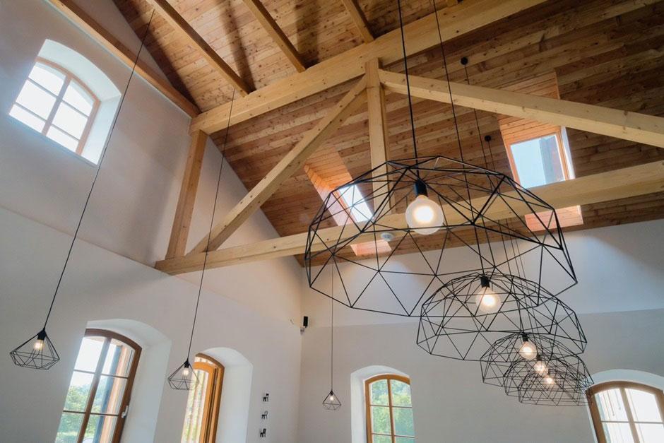 Prirodzené svetlo prúdiace cez strešné a fasádne okná večer nahradí kvalitné umelé osvetlenie. Industriálne drôtené lustre sú ďalším charakteristickým prvkom.