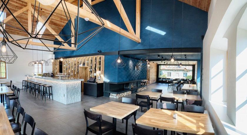 Tmavomodré štukové steny v spojení s bledým drevom zaujímavo dolaďujú interiér reštaurácie.