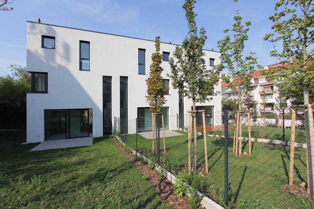 Biela fasáda sesterskej budovy kontrastuje s dreveným obkladom.