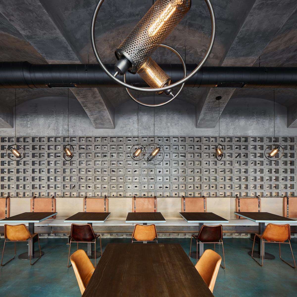 Dekoračná stena z betónových tvárnic so zavesenými uhlíkmi je ústredným motívom interiéru.