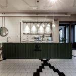 Bar akcentovaný zelenou farbou dominuje materiálovej skladbe zbytku priestoru v béžových odtieňoch.