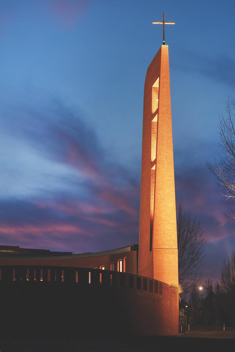 Kostolná veža so zvonicou v podvečernom osvetlení.