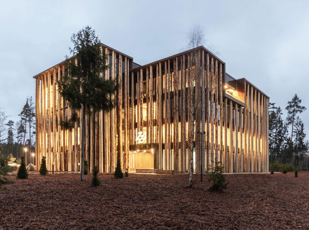 Budova v lese svieti ako lampáš. Ľudia v jej okolí evokujú svätojánske mušky.