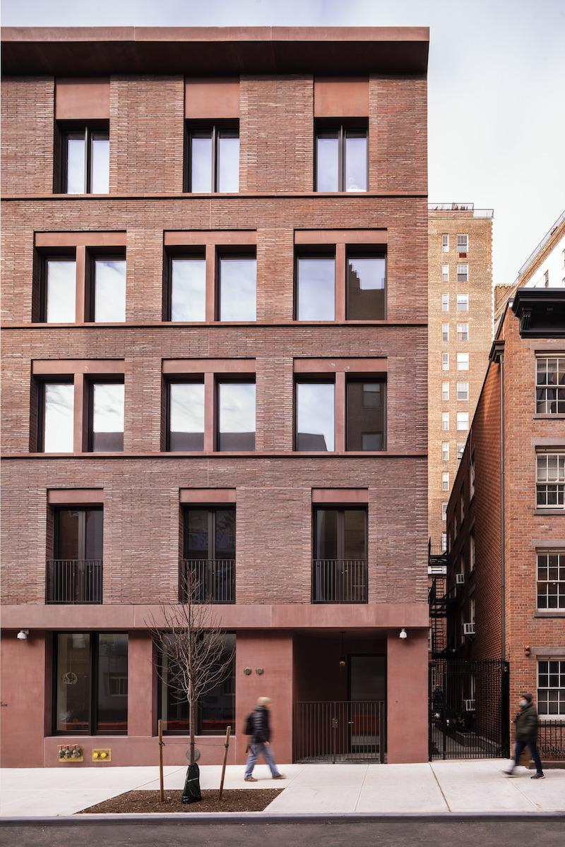 Červený betón v kombinácii s rímskou tehlou začleňuje budovu do okolitej zástavby.