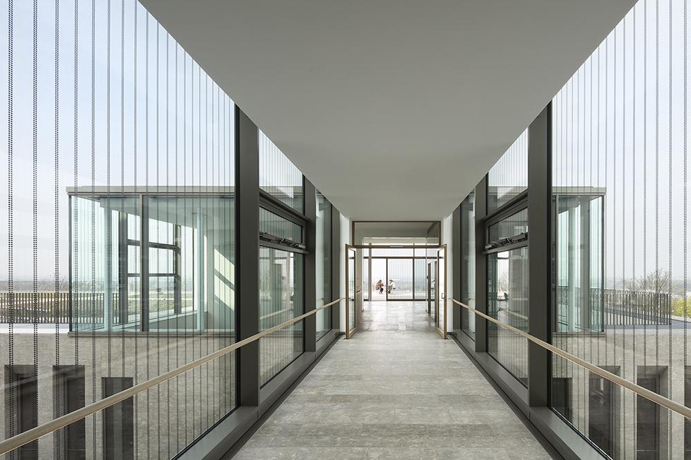 Priestranný sklenený pavilón, ktorý slúži ako salónik uprostred zelenej strechy s výhľadom na údolie Rýna.