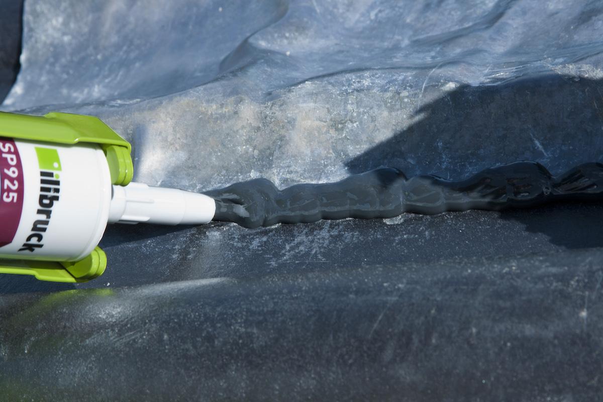 Aplikácia tekutej hydroizolačnej membrány pomocou aplikačnej pištole v mieste oplechovania striech.