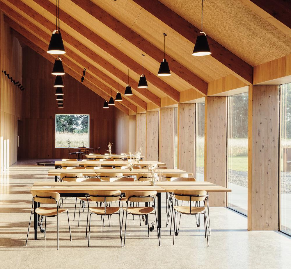 Interiér v tlmenej tonalite dreva bol navrhnutý ako prirodzená súčasť okolitých pšeničných polí.