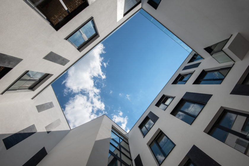 Veľkorysé átrium presvetľujúce spoločné priestory a časť bytov.