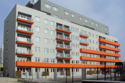 Dom s oranžovým detailom a so zeleným dvorom